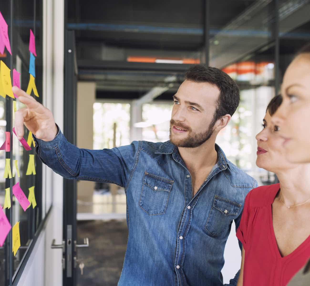 Personen die während eines Workshops etwas an einer Pinnwand besprechen