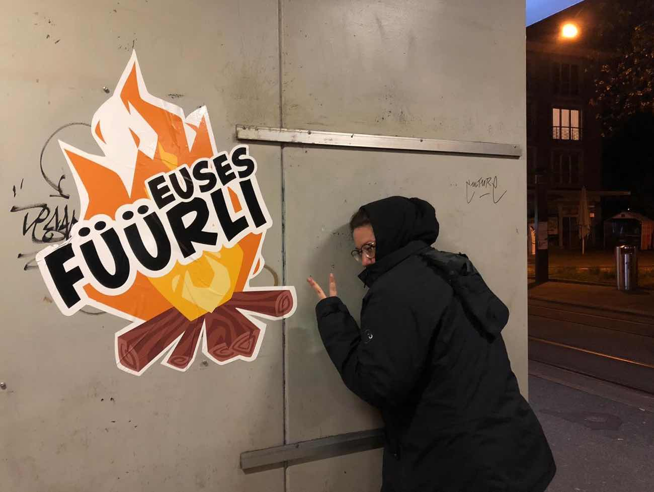 Sticker «Euses Füürli» welche gerade an eine Wand im Baselland geklebt wurde