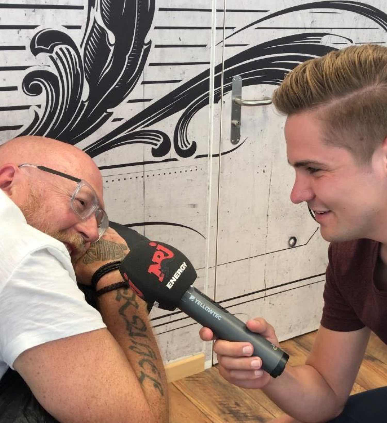 Mann mit I love BL-Tattoo wird interviewt