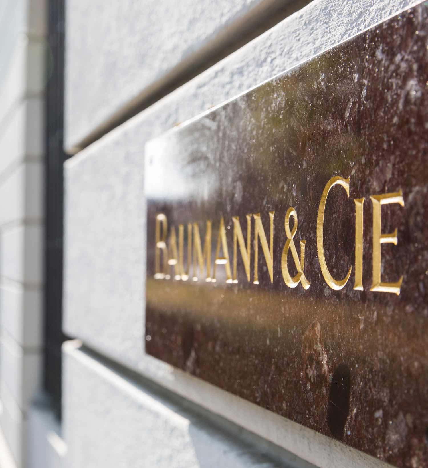 Steintafel mit eingraviertem Namen «Baumann & Cie» an der Hauswand