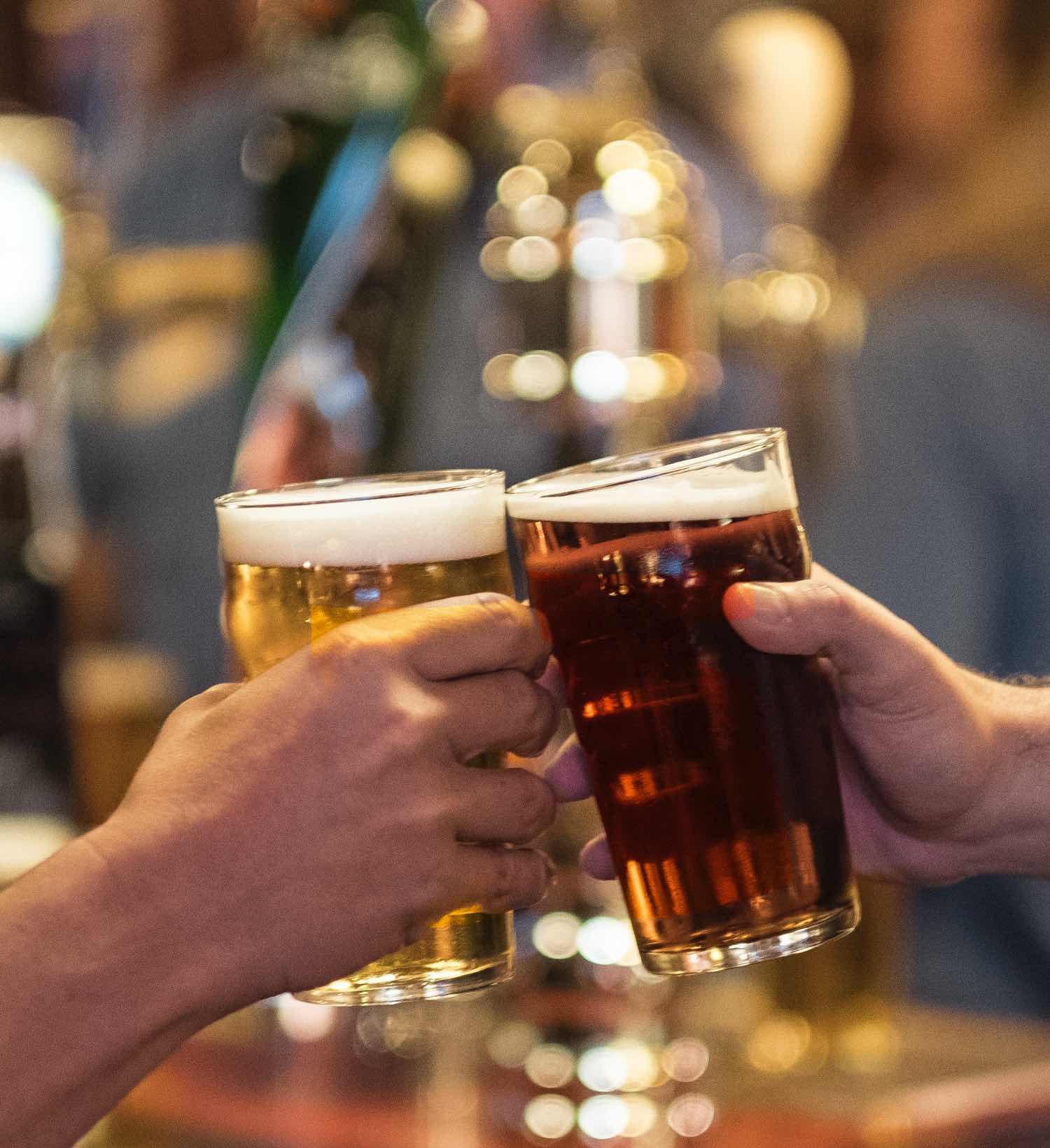 Zwei Personen die mit Bier anstossen