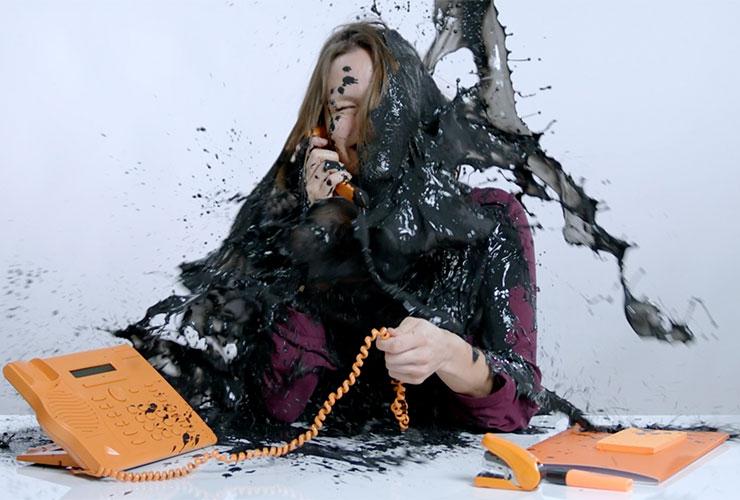 Mind Studios Mitarbeiter am Telefon wird mit Farbe übergossen