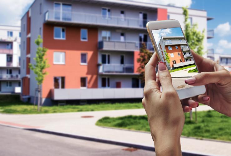 Immobilienvermarktung: Liegenschaft mit Smartphone im Vordergrund